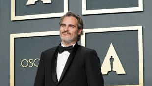 Joaquin Phoenix poses in the press room at the 2020 Oscars with the Best Actor trophy for Joker.