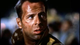"Bruce Willis as ""John McClane"" in Die Hard."