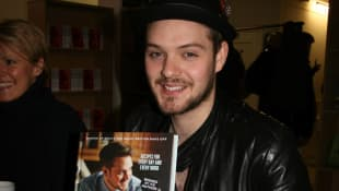 "John Whaite with his book ""John Whaite Bakes"" in London, 2014."