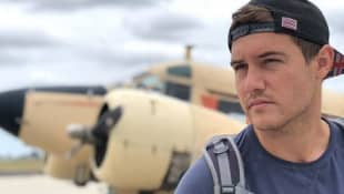 Peter Weber poses on the runway of an airport. He is going to be the next Bachelor.