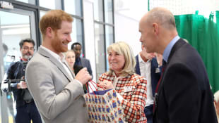 Prince Harry accepting a baby gift at the Youth Zone from Lady Jane Woodward, a long-time family friend.