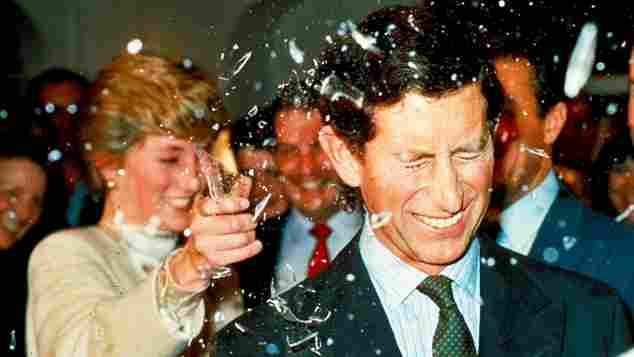 Princess Diana breaks a sugar glass bottle over her husband's head at Pinewood Studios to watch the making of the latest James Bond films on 11 December 1986.