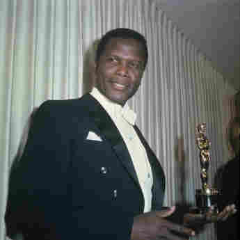 Bahamian American actor Sidney Poitier holding his Academy Award for Best Actor in a Leading Role in 1964